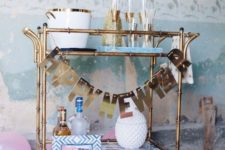 07 a brass bar cart with a shiny letter garland is all you need for party decor