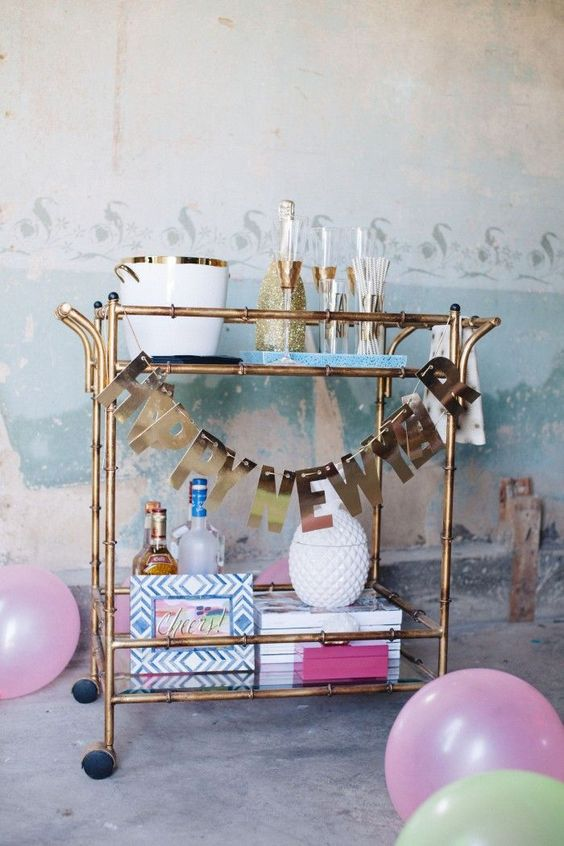 a brass bar cart with a shiny letter garland is all you need for party decor