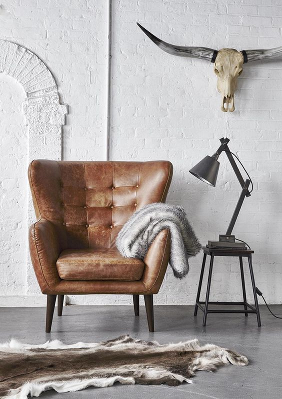 a comfy brown leather armchair plus metal items  for an industrial interior