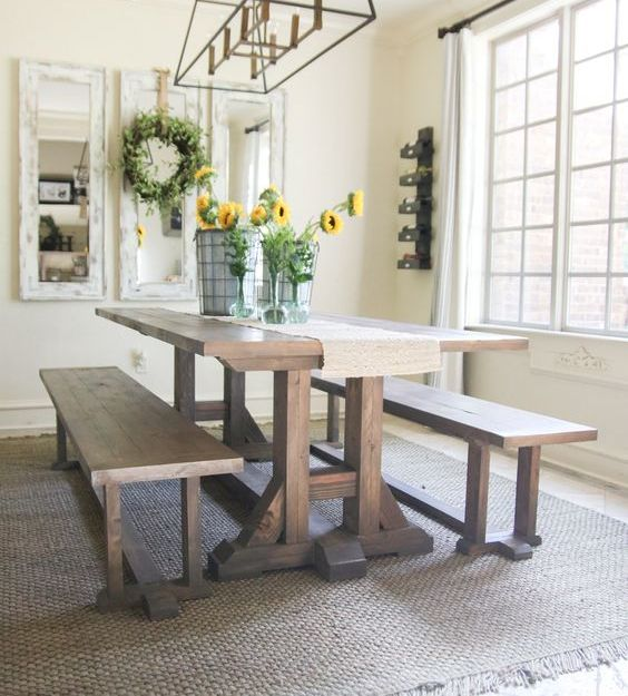 a simple rustic dining space with a trestle dining table and matching benches