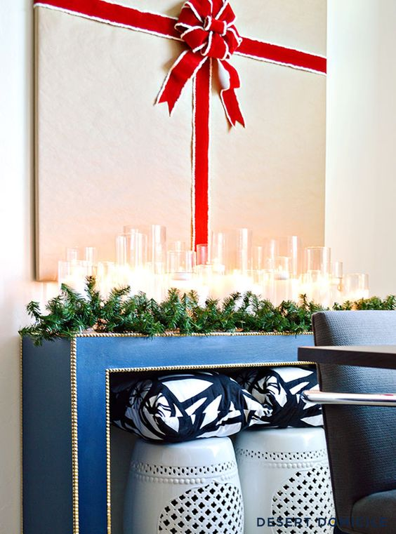 an evergreen garland, lots of candles and a gift artwork over the console look super chic