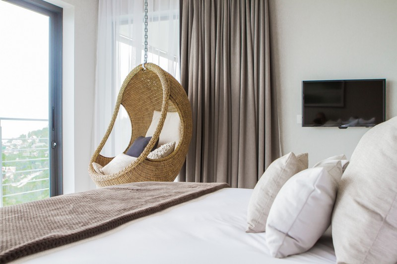 A rattan chair hanging in the bedroom is a cool and fresh idea