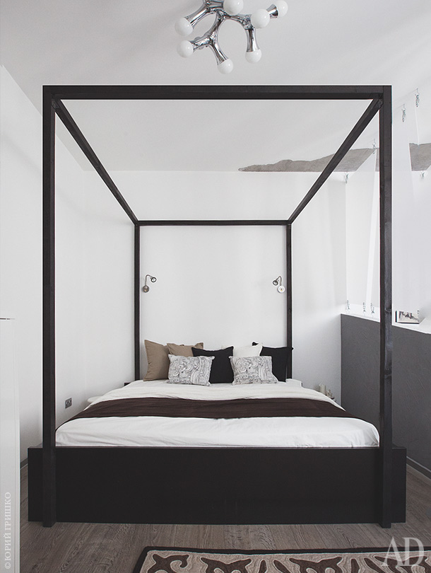 The bedroom is done with a canopy bed and is separated from the living room with a plexiglass divider