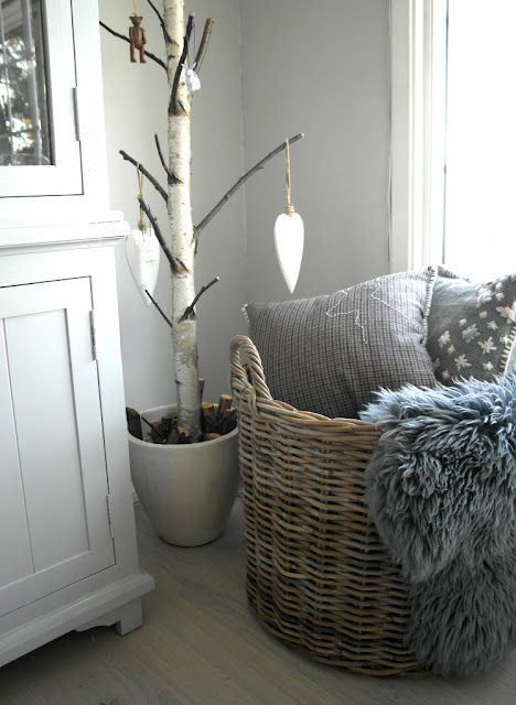 a basket with faux fur and pillows for a Scandinavian bedroom