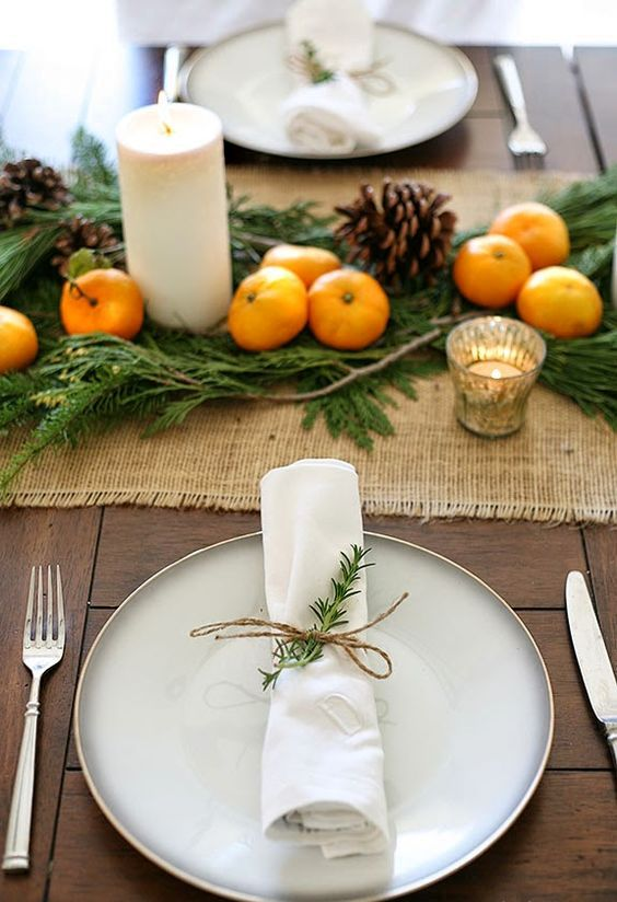 a burlap table runner, citrus, pinecones and candles are great for a rustic tablescape