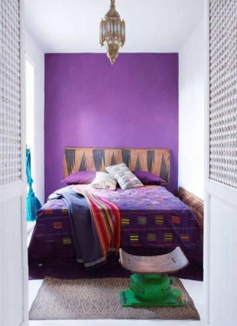 a violet wall for a statement in the bedroom and matching bedding for a bold look