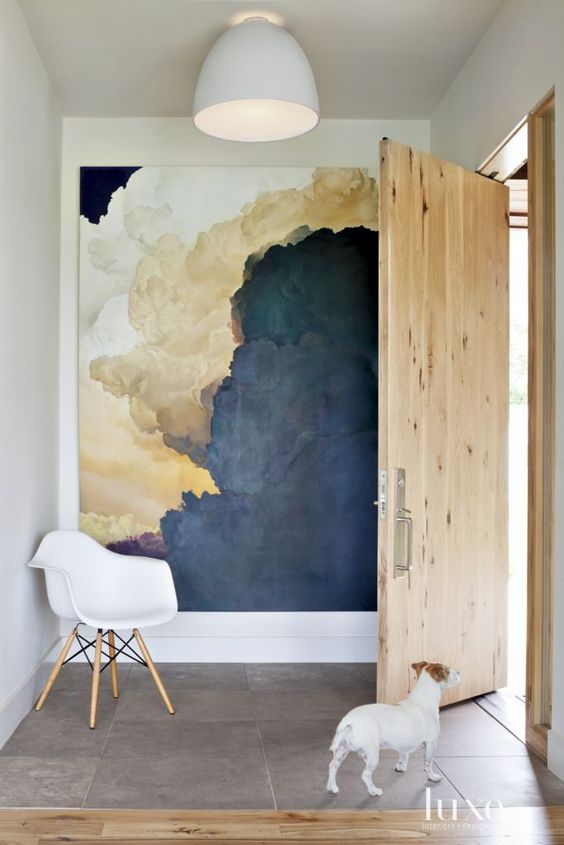 an oversized abtract artwork takes the whole blank wall and makes the entryway interesting