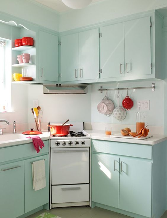 mint-colored cabinets and some bold tableware is all you need to create a retro feel