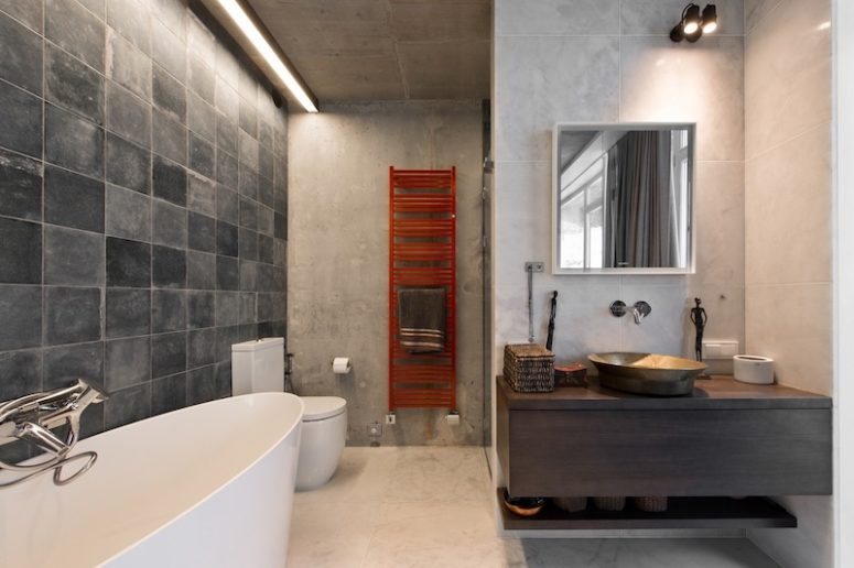 A red radiator reminds of the rugs in the bedroom, and concrete-like tiles add a modern touch here