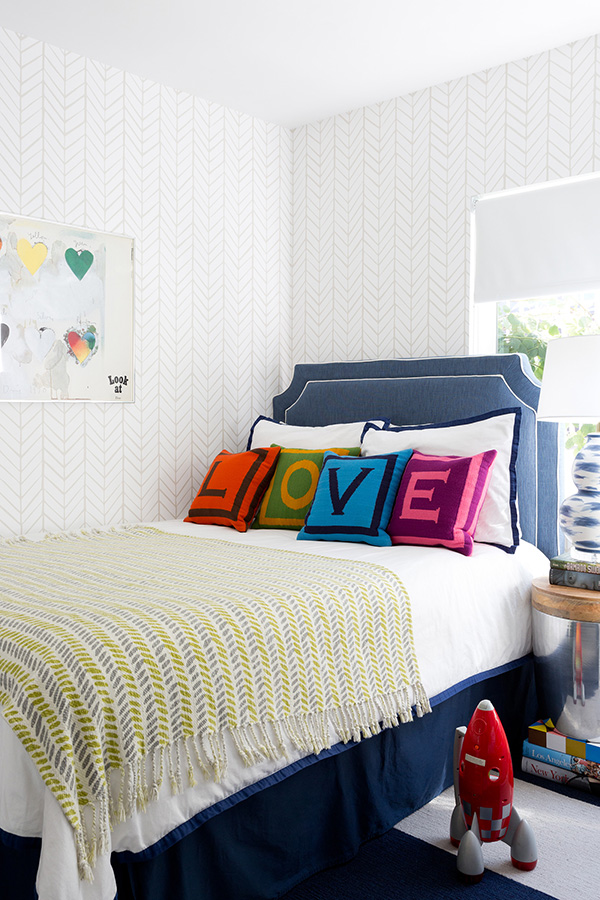 The kids' room is airy and light-colored, and bold shades are brought with pillows