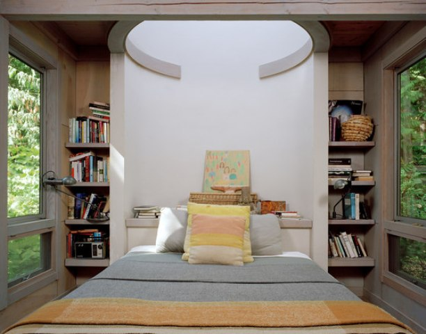 The master bedroom features bookshelves on both sides and a skylight above the bed