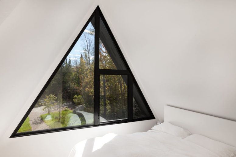 The master bedroom is pure white, with a pretty triangle window and a comfy bed