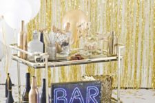 09 a brass bar cart with white and gold balloons, black and gold bottles and a neon sign