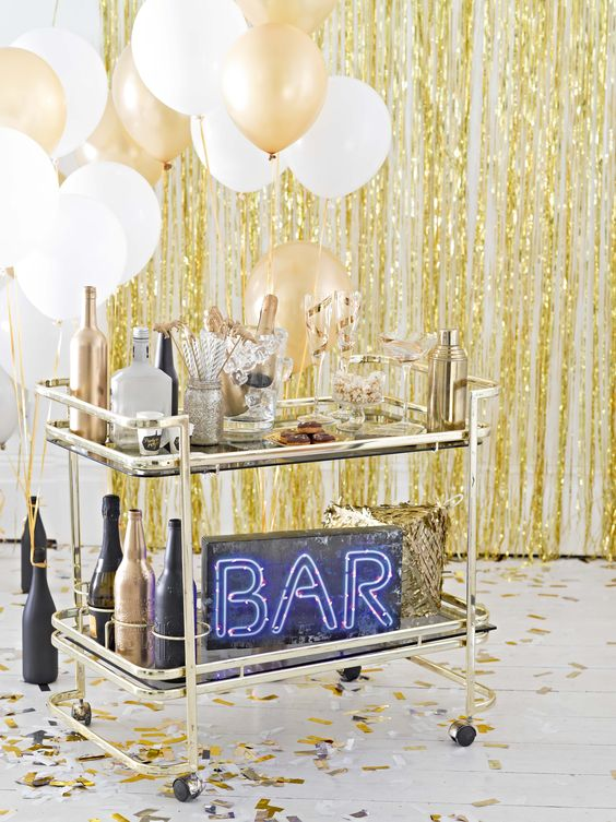 a brass bar cart with white and gold balloons, black and gold bottles and a neon sign