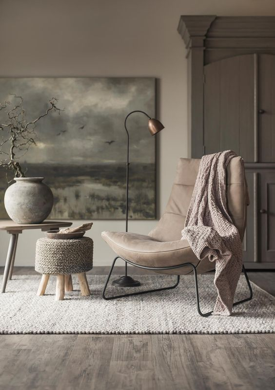 a chic beige leather modern chair on metal legs and a metal floor lamp for a chic reading nook