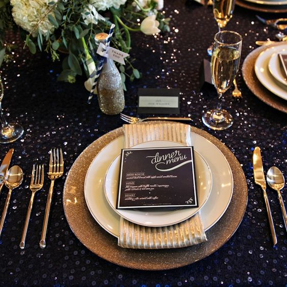a dark sequin tablecloth, gold glitter chargers, gold cutlery and a lush greenery and bloom centerpiece