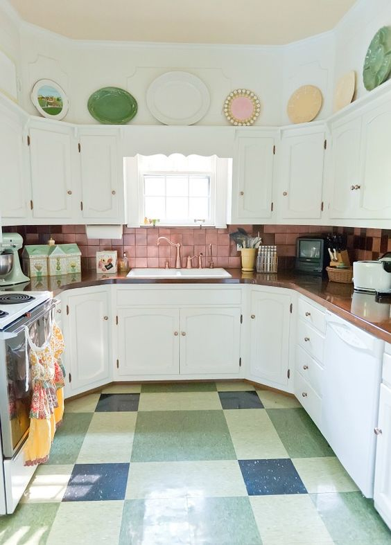 a pink tile backsplash, a colorful tile floor and bold dishes over the cabinets