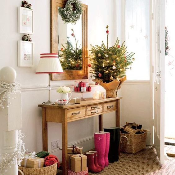 an evergreen tree with ornaments and lights and a gift display are all you need for cute Christmas decor