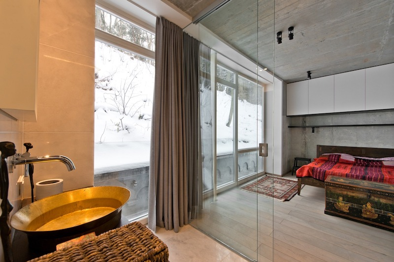 The bedroom is separated only with glass doors from the bedroom