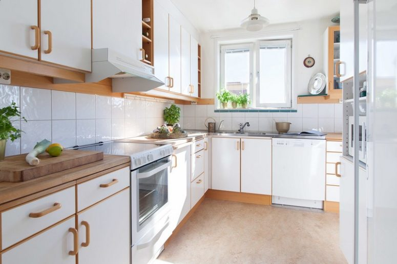 The kitchen features white cabinets and natural wood touches that make the space comfier