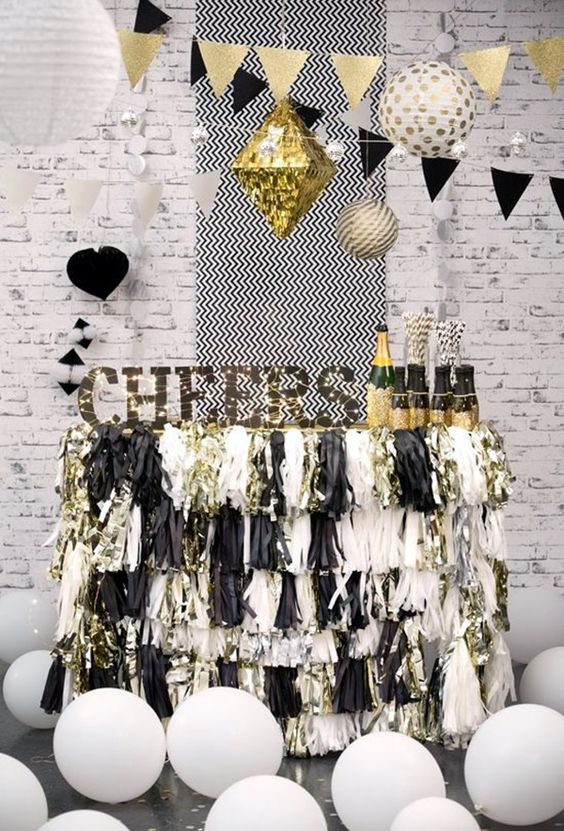a cheerful black and silver sparkly fringe bar cart with a sign and lights and balloons around