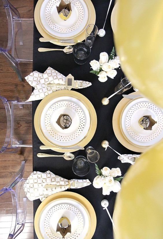 a chic black and gold tablescape with polka dots, geo prints and some white blooms