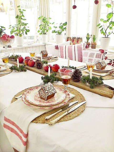 a cozy rustic tablescape with gingerbread house cookies, evergreens, pinecones, apples and candles