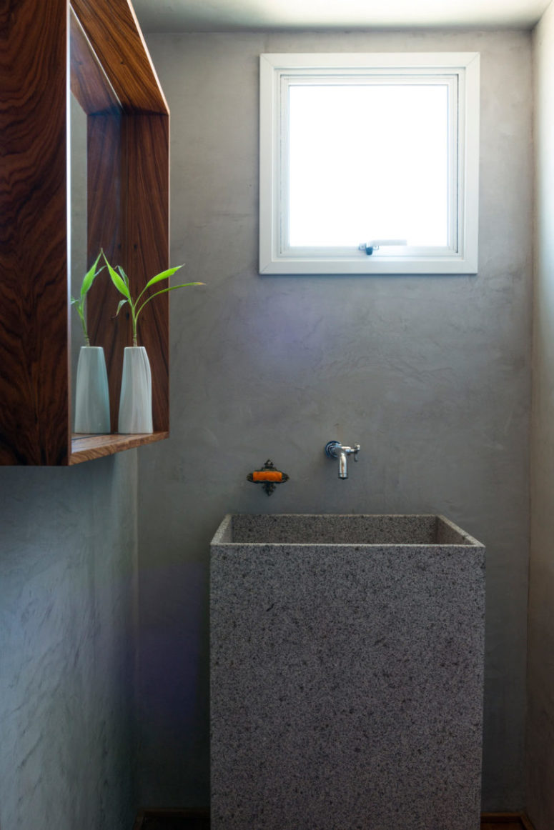 The bathroom is done with concrete, with stone and wood