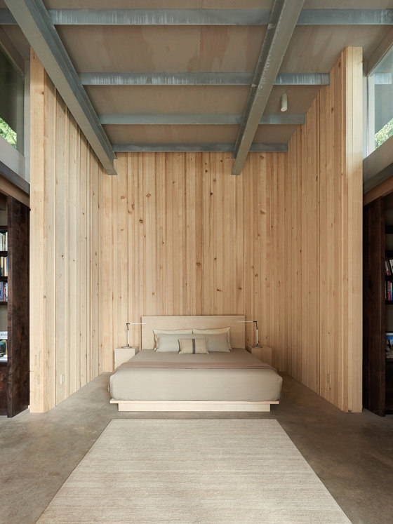 The guest bedroom is clad with natural wood and there's an upholstered creamy bed
