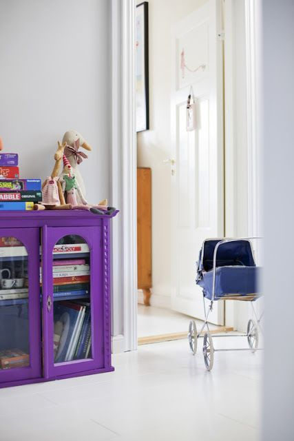 a bold violet bookcase placed right on the floor is a cool idea for any space