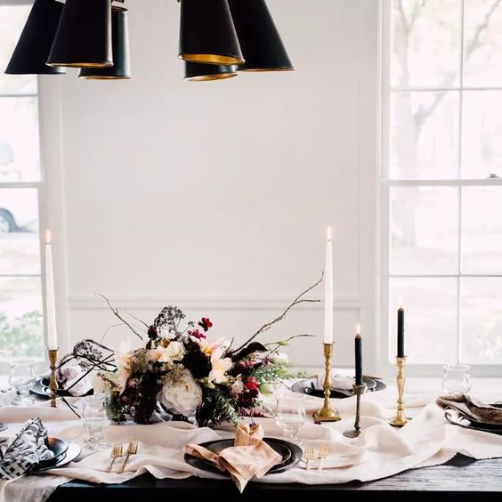 a chic black and white tablescape with gold touches, a textural bloom centerpiece and black plates, a neutral table runner