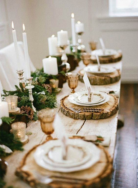 a lush garland with pinecones and candles, wood slice chargers and amber glasses for an elegant rustic tablescape