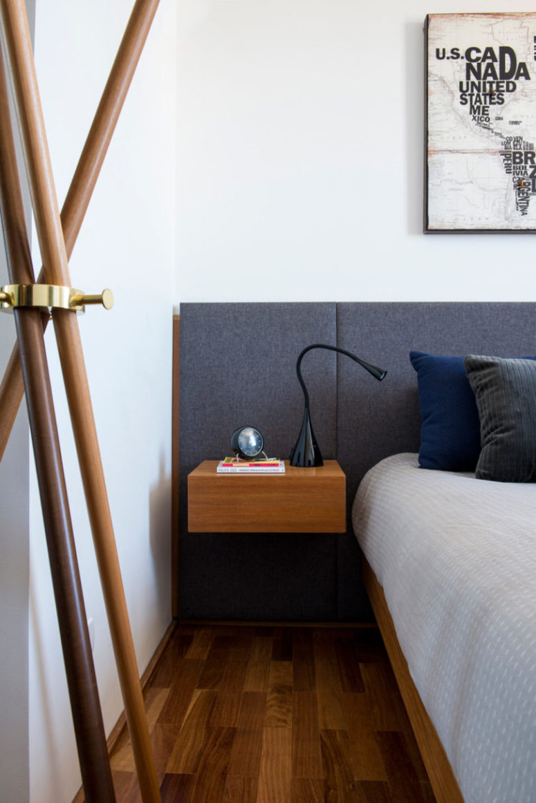 The bedroom shows off an upholstered headboard, a floating bed and nightstands