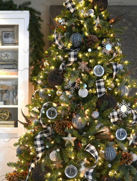 a black and white Christmas tree with pinecones, lights and buffalo check ornaments and garlands
