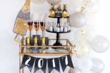 12 a copper bar cart with white and grey balloons, a banner and glitter bottles and glasses