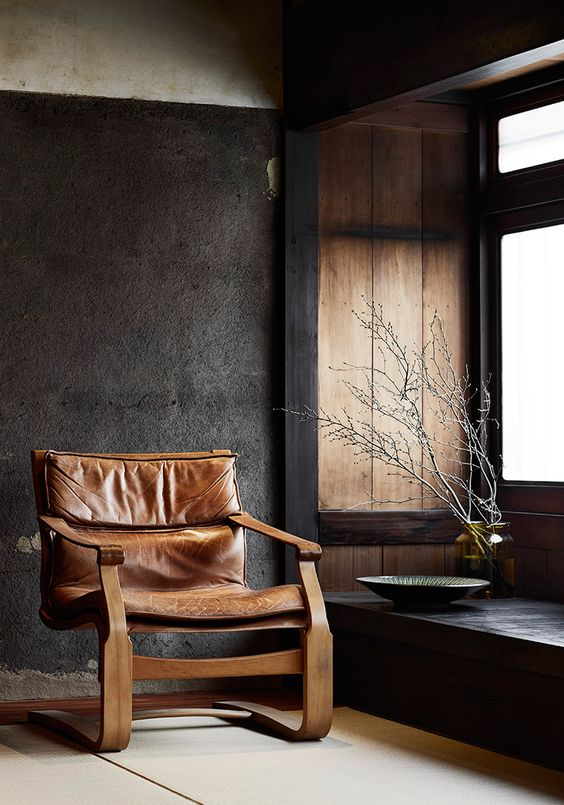 a fantastic leather chair with a wooden frame of an interesting shape looks very eye-catching