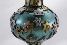 12 a metal Christmas ornament with metal stars, gears, grommets and other details
