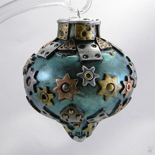 a metal Christmas ornament with metal stars, gears, grommets and other details
