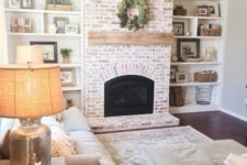 12 a whitewashed red brick fireplace with a wooden mantel for a neutral rustic space