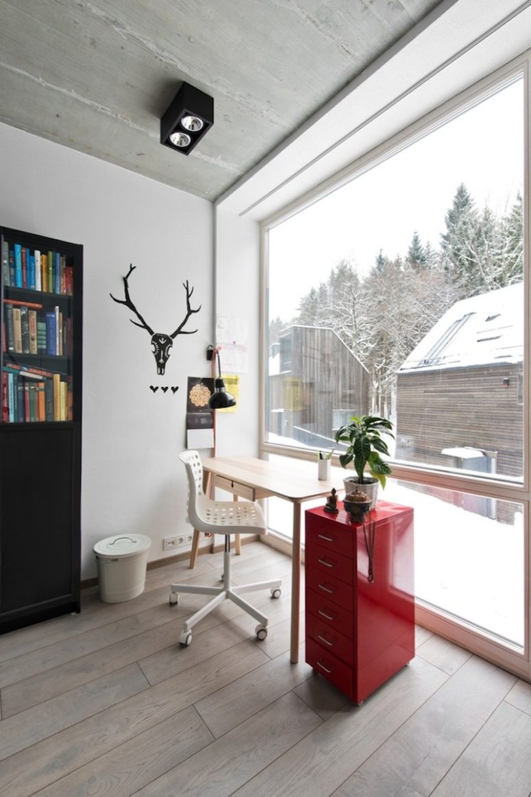 The home office features red and black touches and a large window to enjoy the views