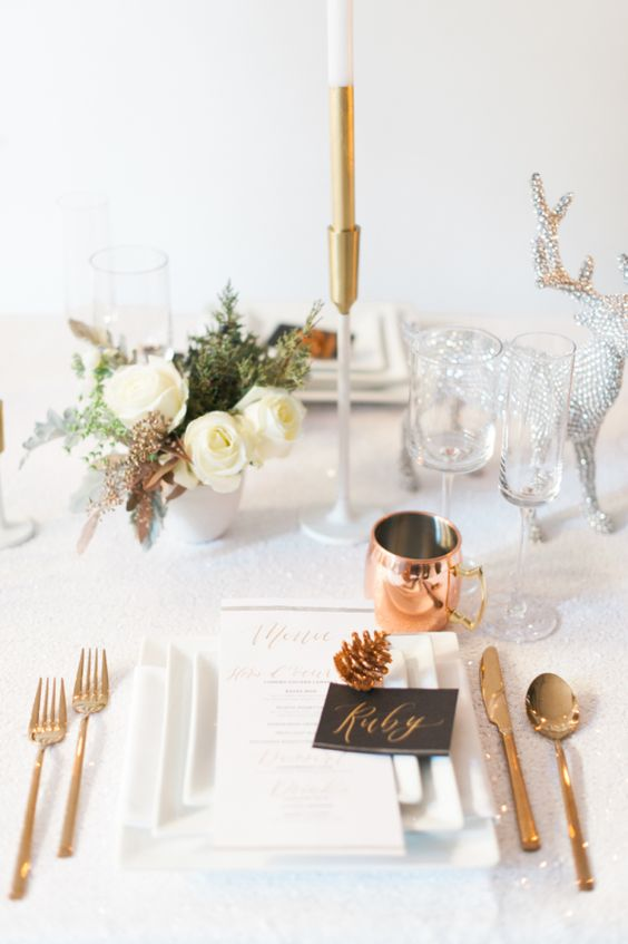 a chic holiday tablescape with white blooms, copper cutlery and mugs and a silver deer figurine for a sparkly touch