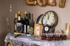 13 a drink station decorated with silver fringe, a glitter garlands, gold balloons and disco balls