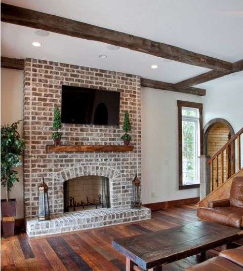a rustic barn space with a dark yet whitewashed brick fireplace