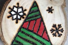 13 a wood burnt and painted Christmas ornament with snowflakes and a geometric tree
