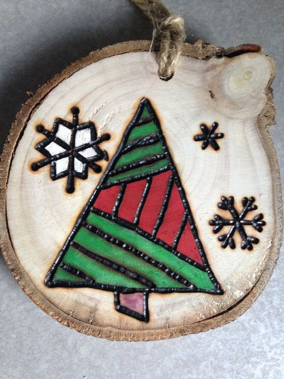 a wood burnt and painted Christmas ornament with snowflakes and a geometric tree