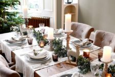 14 a chic neutral tablescape with candles, evergreens, deer figurines, faux birds and branches