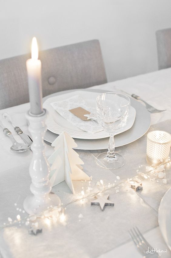 a clean white tablescape with a dove grey table runner, LEDs, stars, candles and wooden fir trees