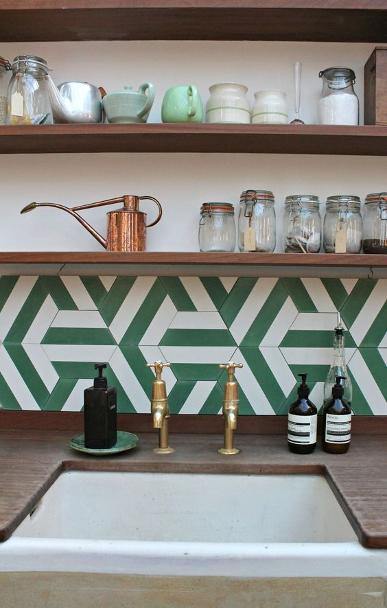 a green and white geometric tile backsplash looks very retro-inspired
