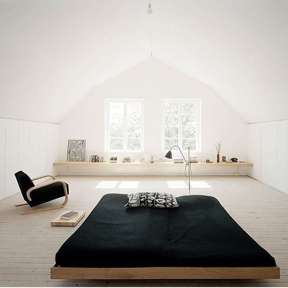a low Japanese bed and a functional modern chair, black textiles create a contrast