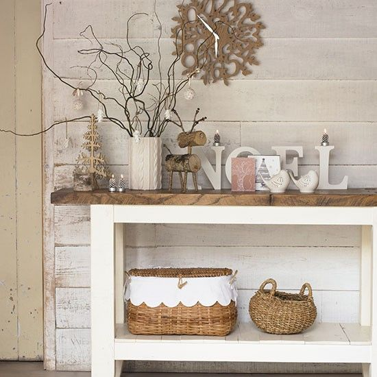 a rustic console with wooden and wicker decor, with letters and bracnesh in a cable knit vase